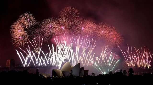 Fireworks explode over the Harbour Bridge and the Opera House during New Year's Eve celebrations in Sydney, Australia, Wednesday, January 1, 2014. (Photo by Rob Griffith/AP Photo)