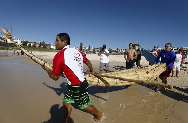 """Australian champion surfer Cheyne Horan (R) guides Peruvian surfer Carlos """"Huevito"""" Areola, carrying his reed board, or """"caballito"""" (little horse), into the ocean at Sydney's Bondi Beach, February 24, 2016. (Photo by Jason Reed/Reuters)"""
