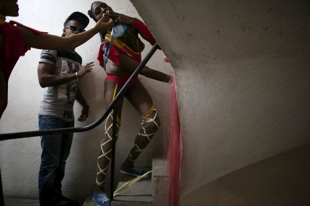 """A dancer smokes a cigarette at the backstage of a cinema where the """"Cuerda Viva"""" (Live Strings) alternative music festival is taking place, in Havana, February 26, 2016. (Photo by Alexandre Meneghini/Reuters)"""