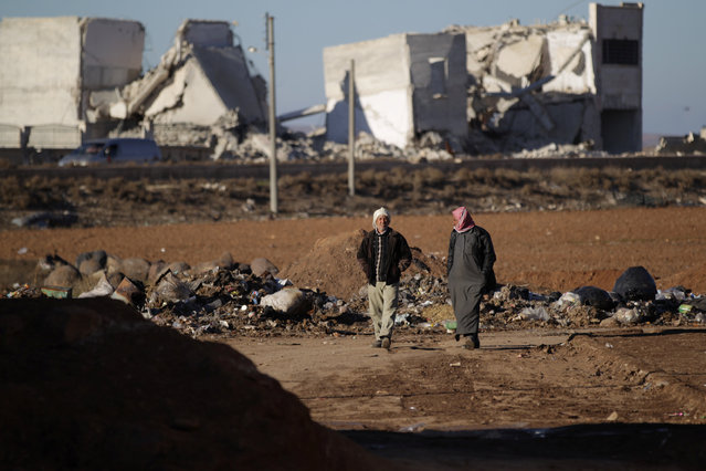 Men walk near damaged buildings in al-Rai town, northern Aleppo countryside, Syria January 13, 2017. (Photo by Khalil Ashawi/Reuters)