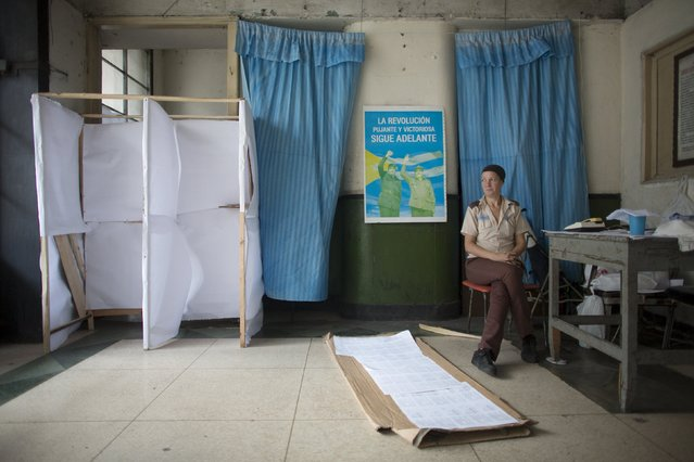 Caretaker Adriana Haedo, 40, sits beside a poster of former Cuban leader Fidel Castro (L) and his brother President Raul Castro at a polling station to be used for the municipal elections, in Havana April 18, 2015. (Photo by Alexandre Meneghini/Reuters)