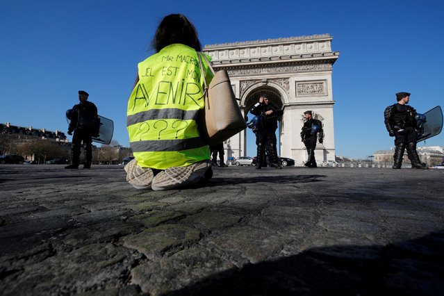 """A protester wearing a yellow vest kneels on the Champs Elysees near the Arc de Triomphe during a demonstration by the """"yellow vests"""" movement in Paris, France, February 23, 2019. Message reads, """"Mr Macron, What is my Future"""". (Photo by Philippe Wojazer/Reuters)"""