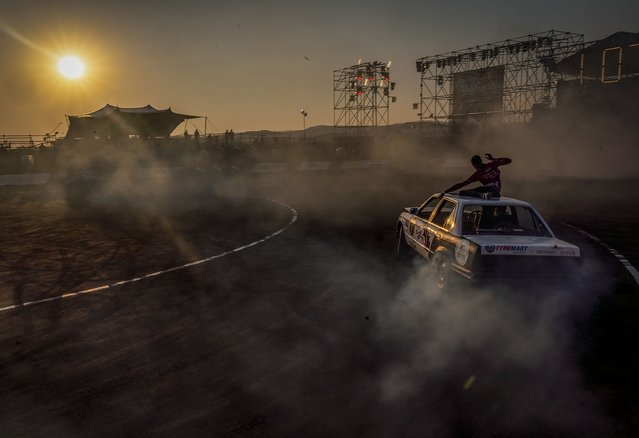 Redwan Hoff sits on the roof of a BMW while driver Lorenzo Dada competes in the Redbull Shay iMoto, a spinning event where twelve of the best spinners from South Africa gather to showcase their spinning skills and stunts in Johannesburg, Friday, September 10, 2021. (Photo by Shiraaz Mohamed/AP Photo)