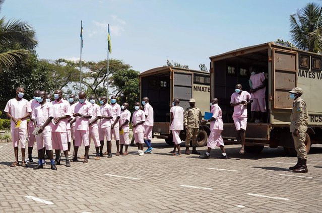 Prison warders guard some 20 accused for terrorism at the Supreme Court in Kigali, Rwanda on September 20, 2021. (Photo by Simon Wohlfahrt/AFP Photo)
