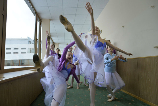 Students perform in a hallway before the start of a class in the Moscow State Academy of Choreography, better known as the Bolshoi Ballet Academy, in Moscow, on March 3, 2016. (Photo by Yuri Kadobnov/AFP Photo)