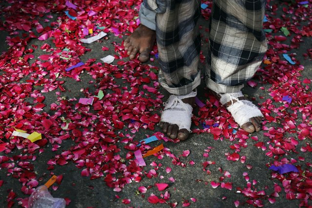 An Indian Sufi Muslim devotee, who arrived walking barefoot from New Delhi, stands on a road covered with rose petals thrown by locals during a procession as part of the Urs festival at the shrine of Sufi saint Khwaja Moinuddin Chishti in Ajmer, India, Sunday, April 19, 2015. (Photo by Deepak Sharma/AP Photo)