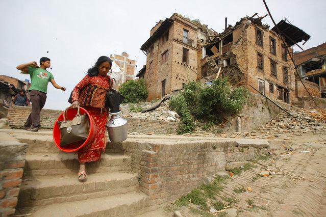 Nepalese evacuate with belongings to safer areas in Bhaktapur, Nepal, Sunday, April 26, 2015. (Photo by Niranjan Shrestha/AP Photo)