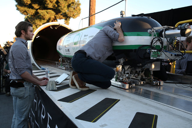 Team members from Delft Hyperloop, Delft University of Technology place their pod on the track during the SpaceX Hyperloop Pod Competition in Hawthorne, Los Angeles, California, U.S., January 29, 2017. (Photo by Monica Almeida/Reuters)