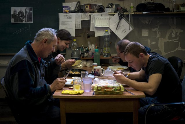 Car mechanic Adrienn Jandzso (2-L) eats lunch with her colleagues in the repair workshop of the Veszprem Department of the National Ambulance Service in Veszprem, 108 kms southwest of Budapest, Hungary, 25 February 2016. (Photo by Bea Kallos/EPA)