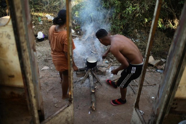 "Venezuelans Hildemaro Ortiz and Ixora Sanguino cook outside of an abandoned bus in the border city of Pacaraima, Brazil on April 13, 2019. The bus offers some protection from mosquitoes and the cold of night, Ortiz said. When the bugs get bad, he starts a cardboard fire to smoke them out. He is impatient to move to bustling cities to the south. ""If only this bus had an engine, we would have been on our way to Manaus by now"", he said. (Photo by Pilar Olivares/Reuters)"