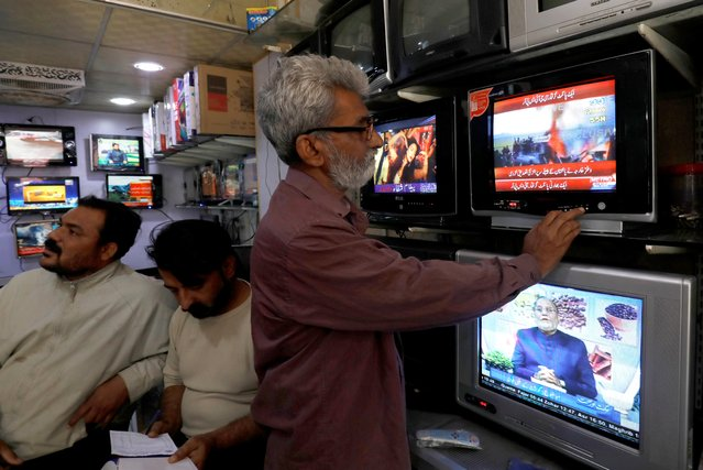 A man looks at a television screen, after Pakistan shot down two Indian planes, at a shop in Karachi, Pakistan February 27, 2019. (Photo by Akhtar Soomro/Reuters)