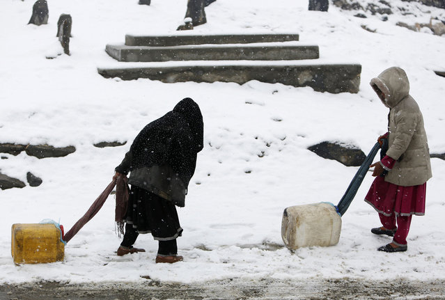 Children drag water containers as it snows in Kabul February 19, 2014. (Photo by Mohammad Ismail/Reuters)