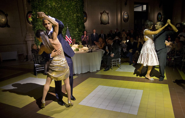 President Barack Obama and first lady Michelle Obama, right, dance the tango with tango dancers during the State Dinner at the Centro Cultural Kirchner, Wednesday, March 23, 2016, in Buenos Aires, Argentina. (Photo by Pablo Martinez Monsivais/AP Photo)