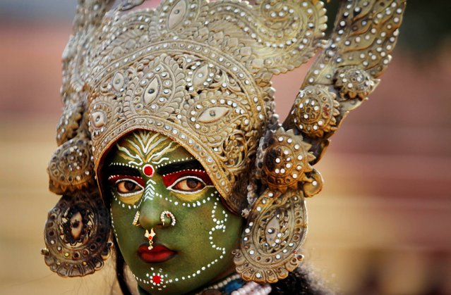 A women dressed as Hindu Goddess Kali participates in a procession on the eve of Shivratri festival, in Jammu, India, Wednesday, February 26, 2014. Shivratri, a festival dedicated to the worship of Hindu God Shiva, will be marked across the country Thursday. (Photo by Channi Anand/AP Photo)