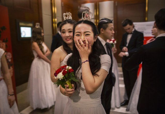 A debutante from a local academy laughs as she and others wait before taking part in the Vienna Ball at the Kempinski Hotel, March 19, 2016, in Beijing. (Photo by Kevin Frayer/Getty Images)
