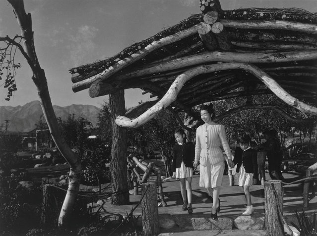 Mrs. Yaeko Nakamura, holding hands with her two daughters, Joyce Yuki Nakamura and Louise Tami Nakamura, walk under a pavilion in a park at the Manzanar War Relocation Center in California, in this 1943 handout photo. (Photo by Courtesy Ansel Adams/Library of Congress, Prints and Photographs Division/Reuters)