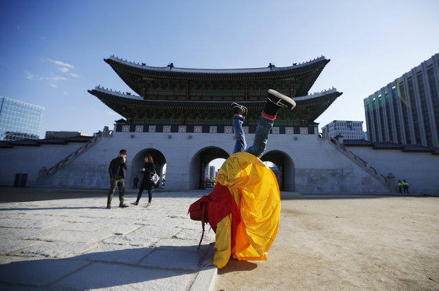 A tourist wearing a traditional costume stands on his hands to pose for a photograph in front of the main entrance of Gyeongbok palace on a sunny winter day in Seoul March 5, 2014. (Photo by Kim Hong-Ji/Reuters)