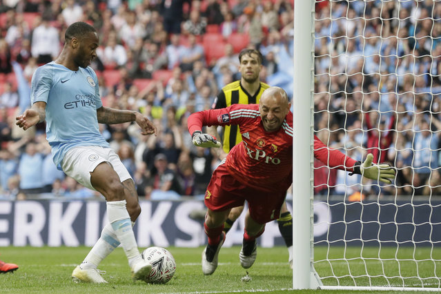 Manchester City's Raheem Sterling, left, scores his side's sixth goal past Watford's goalkeeper Heurelho Gomes during the English FA Cup Final soccer match between Manchester City and Watford at Wembley stadium in London, Saturday, May 18, 2019. (Photo by Tim Ireland/AP Photo)