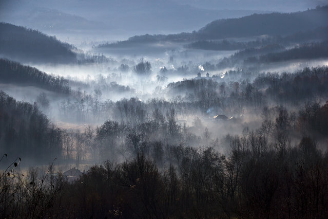 Morning fog engulfs a village outside Izbasesti, Romania, Tuesday, December 16, 2014. Severe fog affected large areas of Romania causing traffic disruptions. (Photo by Vadim Ghirda/AP Photo)