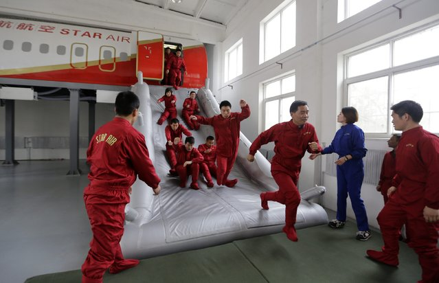 Trainees of the Tianjiao Special Guard/Security Consultant bodyguard training camp practice emergency evacuation from a scale model of a passenger jet  during a special course on flight safety at a flight attendant training centre on the outskirts of Beijing, March 18, 2014. (Photo by Jason Lee/Reuters)