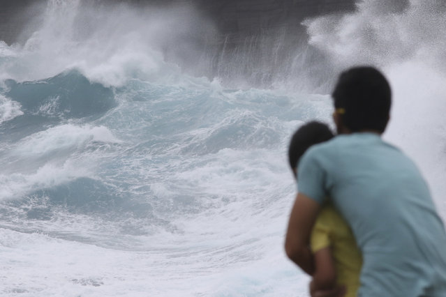 In this August 24, 2018 file photo, a man and his son watch as waves crash off sea cliffs along the southeast shore of Oahu as Hurricane Lane approaches Honolulu. Some of Hawaii's most iconic beaches could soon be underwater  as rising sea levels caused by global warming overtake its white sand beaches and bustling city streets.  That's alarming for a state where beach tourism is the primary economic driver. (Photo by Caleb Jones/AP Photo/File)