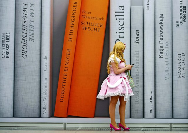 A cosplayer dressed in a fantasy costume stands in front of a poster during the Manga-Comic-Convention at the Leipzig International Book Fair in Leipzig, Germany, on March 15, 2014. (Photo by Jens Meyer/Associated Press)