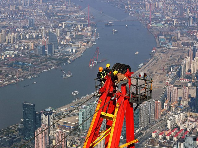 Workers dismantle cranes that have helped to build the Shanghai Tower. (Photo by Rex Features)