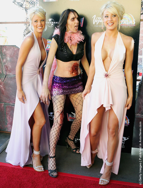 Palms Girls models, twin sisters Ruth Quinn (L) and Ryan Wahrenbrock (R) are joined by an actress dressed as a zombie