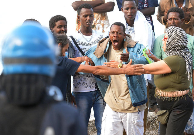 A man shouts as Italian Police remove migrants in Ventimiglia, at the Italian-French border Tuesday, June 16, 2015. Police at Italy's Mediterranean border with France have forcibly removed some of the African migrants who have been camping out for days in hopes of continuing their journeys farther north. The migrants, mostly from Sudan and Eritrea, have been camped out for five days after French border police refused to let them cross. (Luca Zennaro/ANSA via AP)