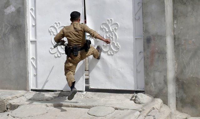 A Kurdish gunman kicks a door as he searches for Shi'ite militiamen during clashes in Tuz Khurmato, Iraq, April 24, 2016. (Photo by Goran Tomasevic/Reuters)