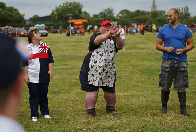 A man wearing an apron with a chicken design catches an egg during the World Egg Throwing Championships and Vintage Day in Swaton, Britain June 28, 2015. (Photo by Darren Staples/Reuters)