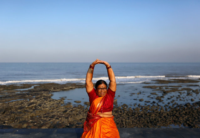 Wearing a saree, traditional women's cloth, a woman exercises on a promenade along the Arabian Sea in Mumbai, India, March 20, 2017. (Photo by Danish Siddiqui/Reuters)