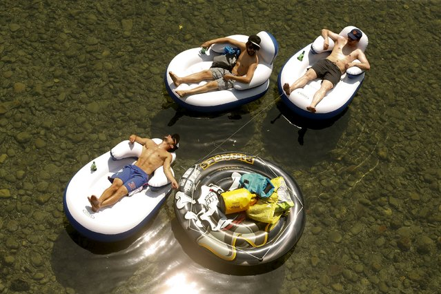 Three men relax as they float in their dinghies during hot temperatures down the Sihl river in Zurich July 3, 2015. (Photo by Arnd Wiegmann/Reuters)
