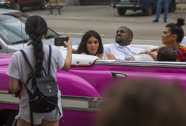 A woman uses her cellphone to take a picture American reality-show star Kim Kardashian West, center, and her husband Kayne West as they ride on a classic car along the streets of Havana, Cuba, Wednesday, May 4, 2016. Rap superstar Kayne West, his wife Kim Kardashian and members of her reality-show-star family have become the latest celebrities to visit Havana. They visited Havana's Museum of Rum Wednesday, stepping out of a hot-pink antique American convertible as they snapped selfies and were recorded by a television crew following them around. At right is Kourtney Mary Kardashian. (Photo by Desmond Boylan/AP Photo)