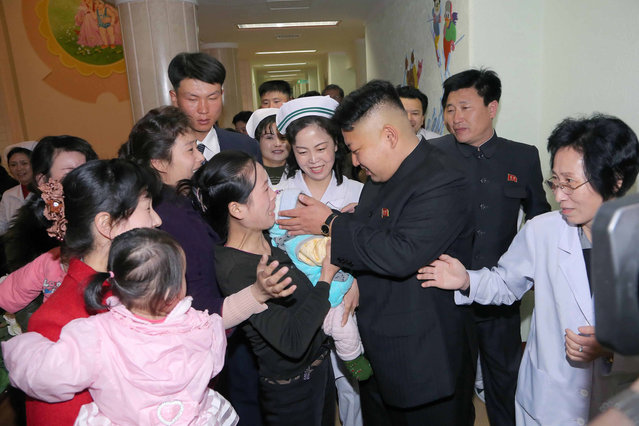 This undated picture released by North Korea's official Korean Central News Agency (KCNA) on March 22, 2014 shows North Korean leader Kim Jong-Un (centre R) meeting people during a visit to the Okryu children's hospital in Pyongyang. (Photo by AFP Photo/KCNA via KNS)