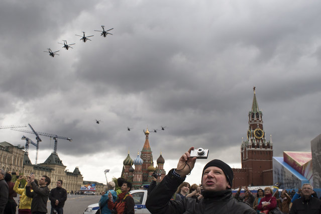 Tourists take pictures while Russian military helicopters fly over the St. Basil's Cathedral, center, and the Spasskaya Tower, right, in Red Square  during a rehearsals ahead of the upcoming Victory Day Parade in Moscow, Russia, Thursday, May 5, 2016. Russians will celebrate Victory in WWII on May 9. (Photo by Alexander Zemlianichenko/AP Photo)