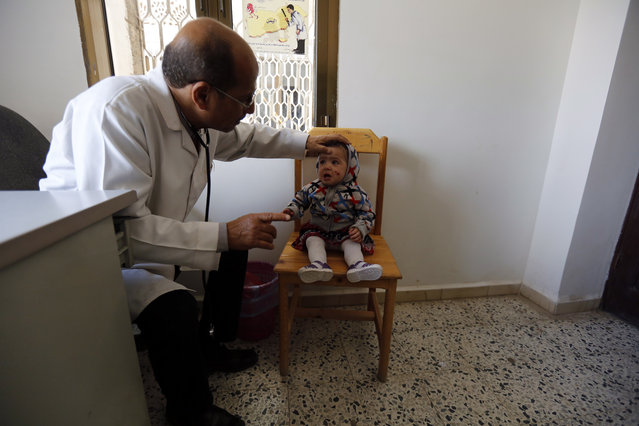 A doctor checks a child at a health center in Sana'a, Yemen, 11 June 2019. According to a recent report of the United Nations Children's Fund (UNICEF), mothers and babies are amongst the most highly vulnerable in Yemen where every two hours, one mother and six newborns die because of complications during pregnancy or birth, due to more than four years of escalating fighting in the Arab country. (Photo by Yahya Arhab/EPA/EFE)