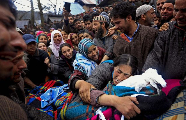 Sumaira Wani, wife of Zia-Ul-Haq mourns by the body of her husband during his funeral in Hirpora, India, on April 25, 2014. Zia, an Indian poll official was killed soon after voting for the ongoing general elections, when suspected rebels fatally shot him and wounded four others in an attack on a bus in the Indian-controlled portion of Kashmir. (Photo by Dar Yasin/Associated Press)