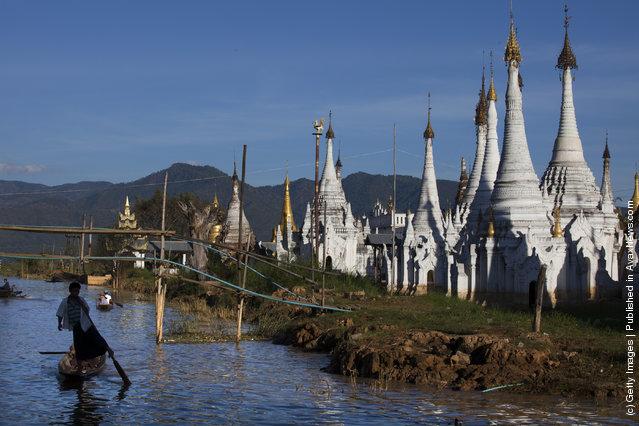 A man paddles his boat past a pagoda along Inle Lake December 16, 2011 in Inle Lake, Myanmar