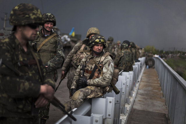 Ukrainian Army soldiers are seen atop of a bridge while Pro Russia civilians block the road in the village of Andreevka, 10 km south of Slavyansk, Ukraine, Friday, May 2, 2014. Russia has massed tens of thousands of troops in areas near Ukraine's border. Kiev officials claim Russia is preparing to invade and that it is fomenting the unrest in the east, where insurgents have seized government buildings in about a dozen cities in towns. (Photo by Manu Brabo/AP Photo)