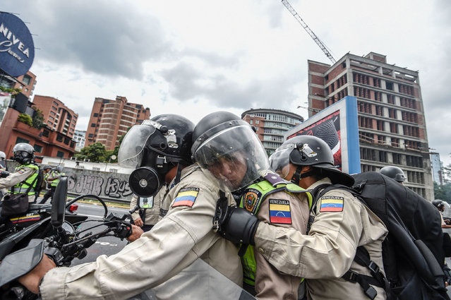 Riot police officers in position to crack down on demonstrators during a protest against Venezuelan President Nicolas Maduro, in Caracas on April 20, 2017. (Photo by Juan Barreto/AFP Photo)