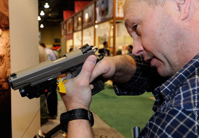 Stuart Craig of Washington tries out a Sig Sauer 1911 model Scorpion pistol at the Sig Sauer booth