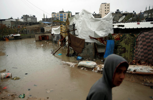 A Palestinian walks through flood water following heavy rain in a neighbourhood in the northern Gaza Strip February 16, 2017. (Photo by Mohammed Salem/Reuters)
