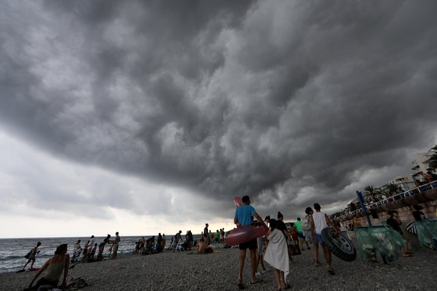People leave the beach as a storm approaches in Nice, France on August 12, 2019. (Photo by Eric Gaillard/Reuters)