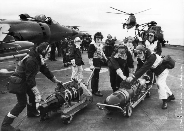 Armourers moving torpedoes on the flight deck of HMS Hermes during the Falklands conflict, May 1982. The torpedos are to re-arm Sea King helicopters to counter the threat from Argentinian submarines