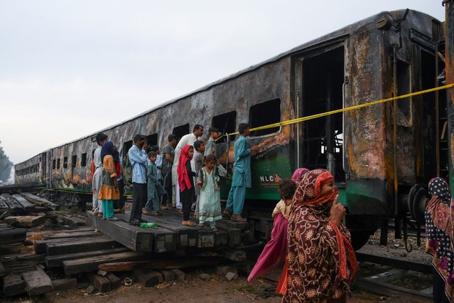 People looks at the burnt-out train carriages a day after a passenger train caught on fire in Rahim Yar Khan on November 1, 2019. Funerals began at dawn in Pakistan on November 1 after a devastating fire ripped through a crowded train carrying religious pilgrims, killing at least 74, with many of the victims resident of one southern town. (Photo by Arif Ali/AFP Photo)