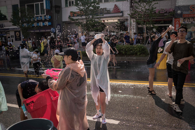 In this photo taken on May 21, 2017, people take part in a water fight organised to mark the opening of the week- long International Mime Festival in Chuncheon. Chuncheon is the capital city of Gangwon province and is located some 80 km east of Seoul. The festival runs until May 28 and features performances involving participants from six countries. (Photo by Ed Jones/AFP Photo)
