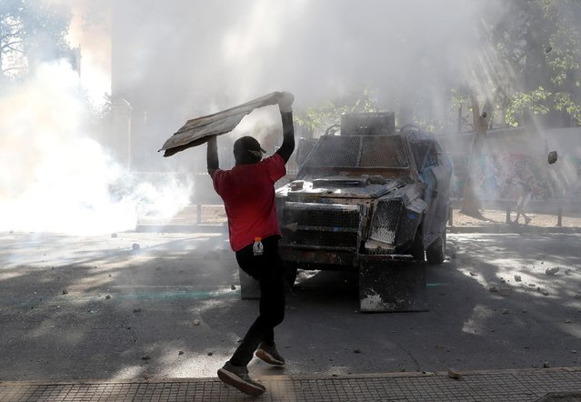 A demonstrator throws an object at police vehicle during a protest against Chile's government in Santiago, Chile on November 19, 2019. (Photo by Goran Tomasevic/Reuters)
