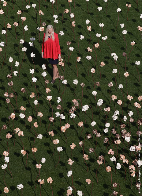 London based Chilean artist Fernando Casasempere poses with his 'Out of Sync' art installation on a grass meadow at Somerset Housein London