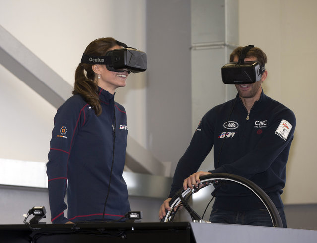 Kate, the Duchess of Cambridge, left, smiles as she joins sailor Ben Ainslie on a simulator, on a visit to the new BAR, Ben Ainslie Racing team base for the America's Cup World Series, in Portsmouth, England, Sunday July 26, 2015. (Photo by Ian Vogler, Pool via AP Photo)